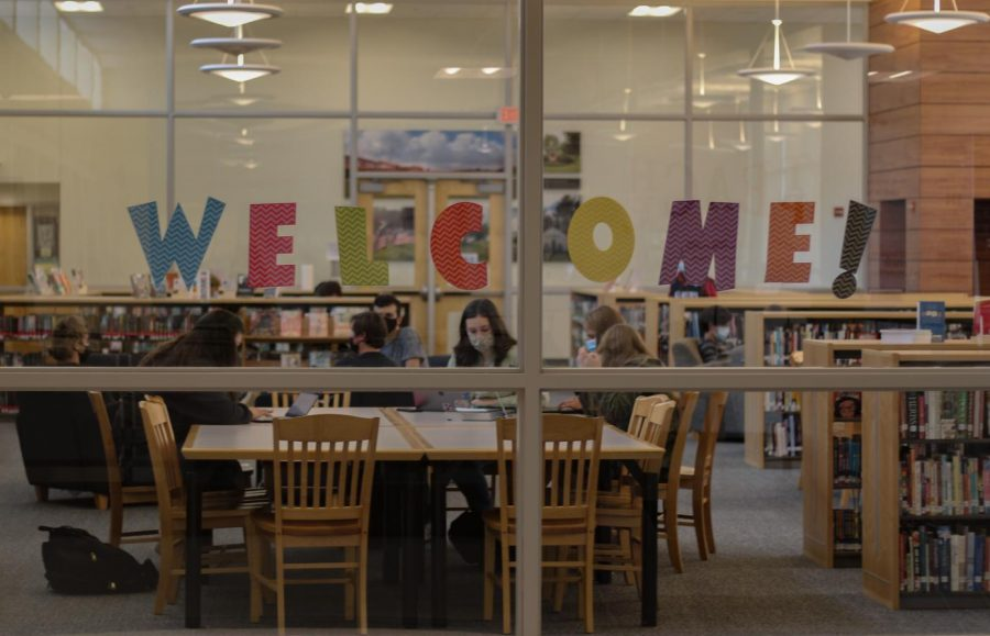 Students study in the library, masks still on